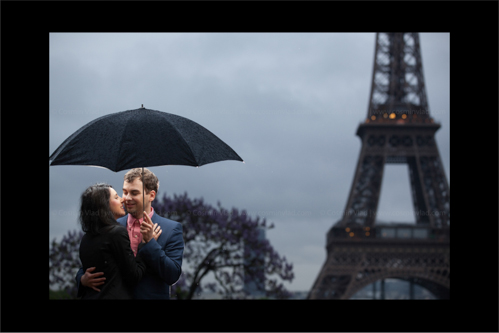 Engaged couple holding tightly and hiding from rain in front of Eiffel Tower