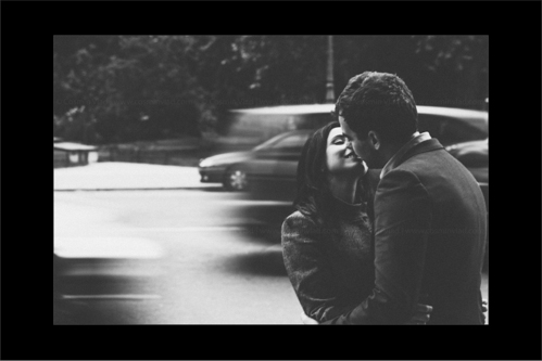 Engaged couple kissing by the side of a road in Paris with cars motion in background