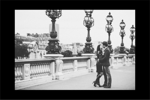 Engaged couple leaning in for a kiss on Pont Alexandre III in Paris