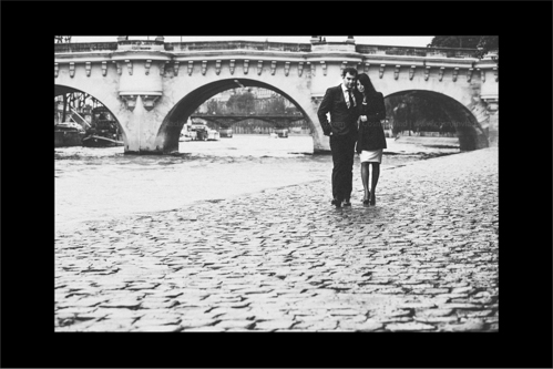 Engaged couple walking holding arms along the Seine in Paris
