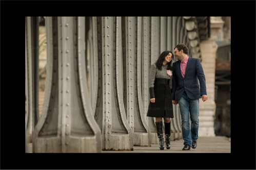 Engaged couple walking along the steel columns of Pont de Bir-Hakeim in Paris holding hands and laughing