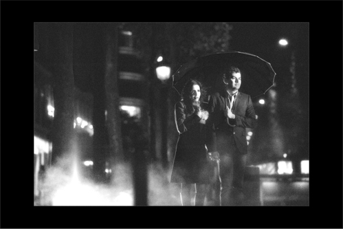 Engaged couple walking on cold and rainy Paris streets in the evening