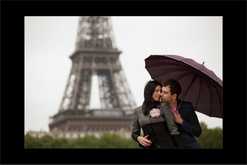 Groom-to-be leaning in for a kiss with his wife-to-be under umbrella in front of Eiffel Tower in Paris