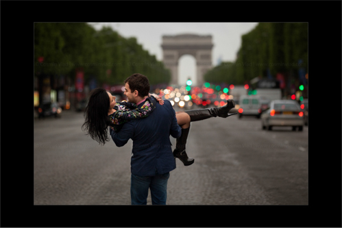 Groom-to-be lifting and spinning around his wife-to-be on the road to Arc de Triomphe in Paris