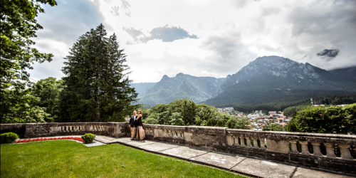 Engaged couple having a great Sinaia landscape behind them at the Peleș Castle