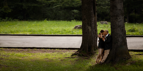 Man leaning against a huge tree and holding dearly his wife-to-be